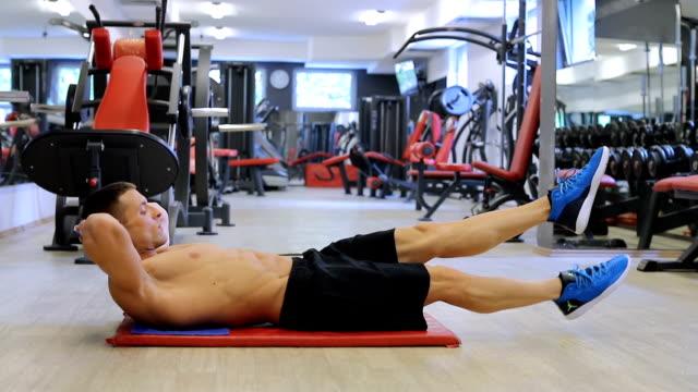 vídeos de stock, filmes e b-roll de lindo apto desportivo homem faz exercícios abdominais na academia - músculo humano