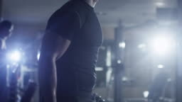 Handsome fit sporty man does dumbbell curl exercises in dark gym.