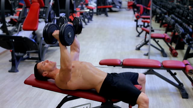 Handsome fit sporty man doing exercises...