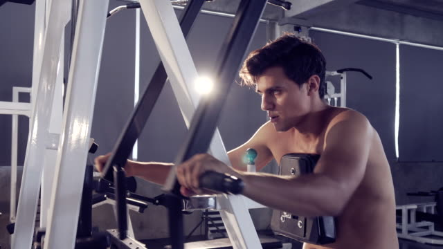 handsome fit sporty man exercises doing machine in dark gym,muscular bodybuilder man - pampering self stock videos and b-roll footage