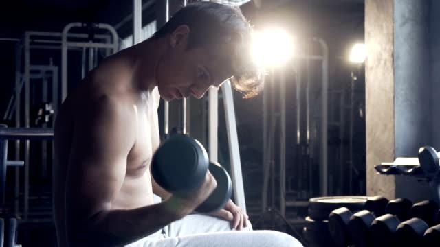 vídeos y material grabado en eventos de stock de guapo hombre deportivo fit ejercicios mancuerna en gimnasio oscuro - mejora personal