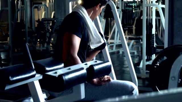 vídeos y material grabado en eventos de stock de guapo hombre deportivo fit dumbell de ejercicios en gimnasio oscuro - mejora personal