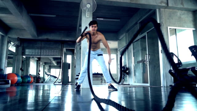 handsome fit sporty man exercises in dark gym - pampering self stock videos and b-roll footage
