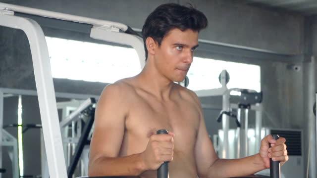vídeos y material grabado en eventos de stock de guapo hombre deportivo fit ejercicios máquina gimnasio oscuro - mejora personal