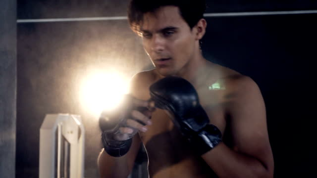 handsome fit sporty man exercises  muay thai boxer fighting in dark gym,muscular bodybuilder man - muay thai stock videos and b-roll footage