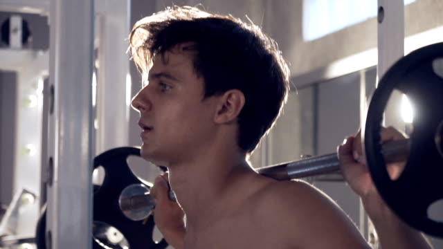 handsome fit sporty man exercises push down on machine in dark gym - pampering self stock videos and b-roll footage