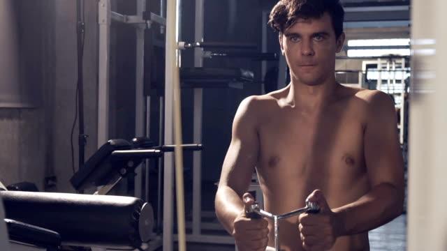 vídeos y material grabado en eventos de stock de ejercicios de guapo deportivo forma levantarse en gimnasio oscuro - mejora personal