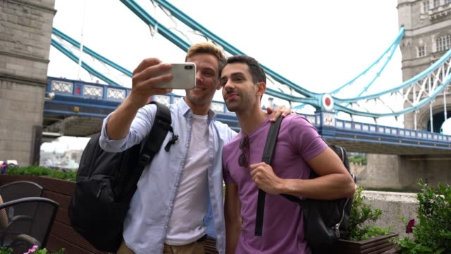 handsome gay student couple at the london bridge taking a selfie embracing each other smiling - tourist stock videos & royalty-free footage