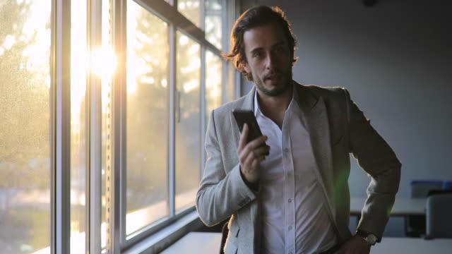 vidéos et rushes de monsieur bel parlant sur le mobile dans le bureau - seulement des jeunes hommes