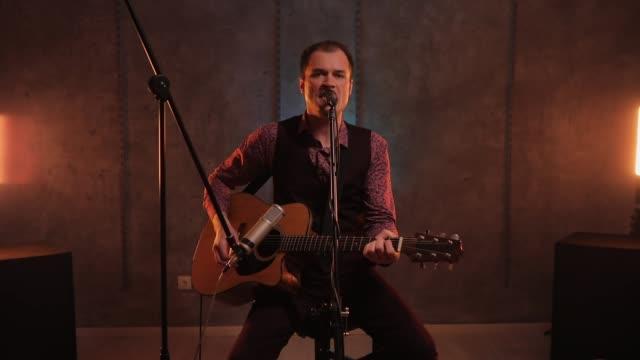 hübscher typ, der akustikgitarre spielt und im musikstudio singt - akkord stock-videos und b-roll-filmmaterial