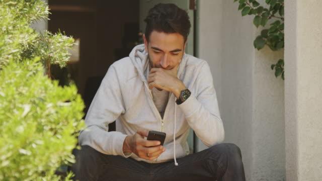 Handsome hispanic man using smartphone outdoors