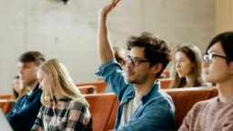 Handsome Hispanic Student Uses Laptop while Listening to a Lecture at the University, He Raises Hand and Asks Lecturer a Question. Multi Ethnic Group of Modern Bright Students.