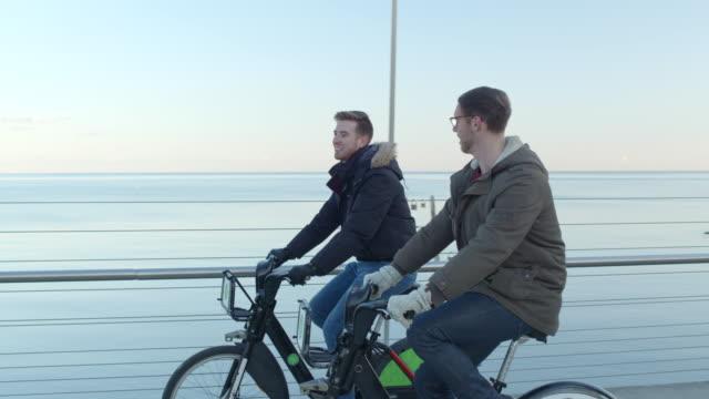 handsome homosexual couple riding bikes - ontario canada stock videos & royalty-free footage