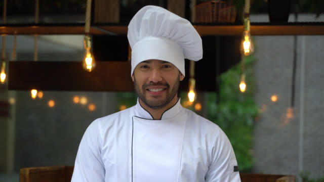 handsome latin american chef wearing a hat smiling at camera - chef's hat stock videos and b-roll footage