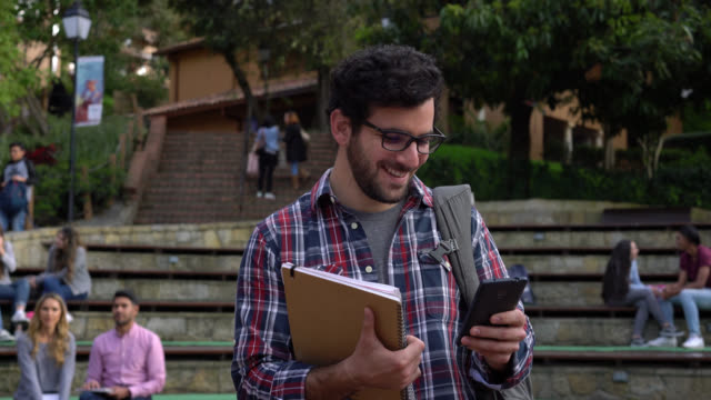 handsome latin american male student chatting on his smartphone while walking around campus - campus stock videos & royalty-free footage