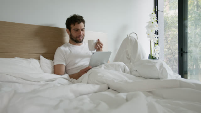 handsome latin american man relaxing on bed drinking tea and reading something on tablet - duvet stock videos & royalty-free footage