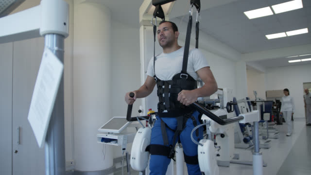 handsome male patient on a exoskeleton robot at rehab learning to walk again looking focused - exoskeleton stock videos & royalty-free footage