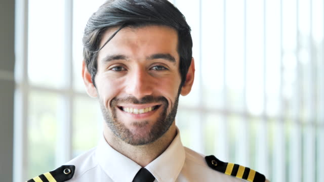 handsome man aircraft pilot looking a camera at airport. - one young man only stock videos & royalty-free footage