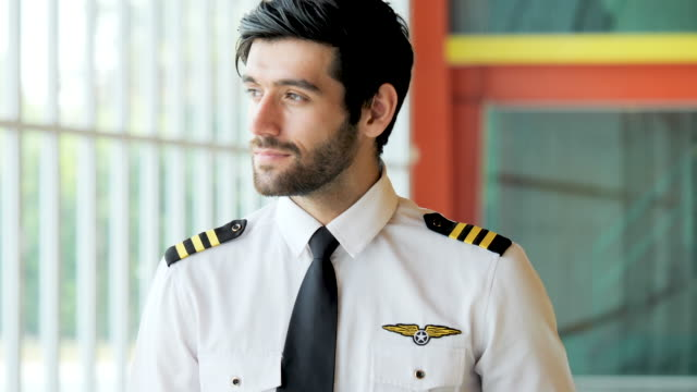 handsome man aircraft pilot looking a camera at airport. - captain stock videos & royalty-free footage