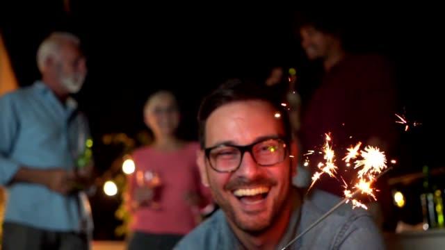 vidéos et rushes de bel homme célébrer une nouvelle année avec amis et famille - serbie
