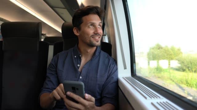 hübsche mann pendelt auf dem zug mit blick auf seine sozialen medien am telefon und genießen die aussicht - bahnreisender stock-videos und b-roll-filmmaterial