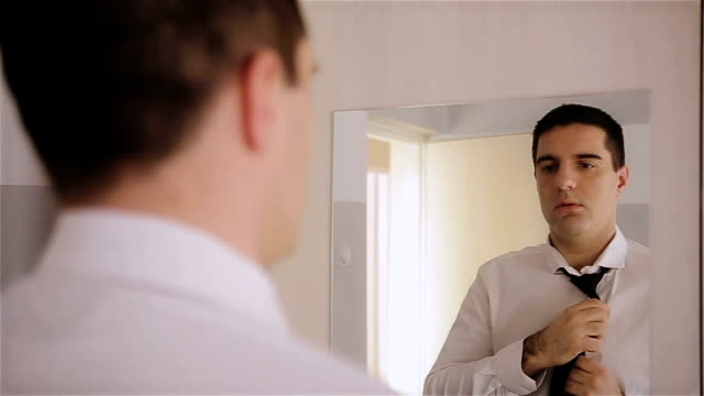Handsome man dressed in modern black formal suit, white shirt and tie getting ready for marketing meeting.