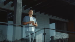 Handsome man drinking coffee in modern exterior outside. Casual man enjoy tea.