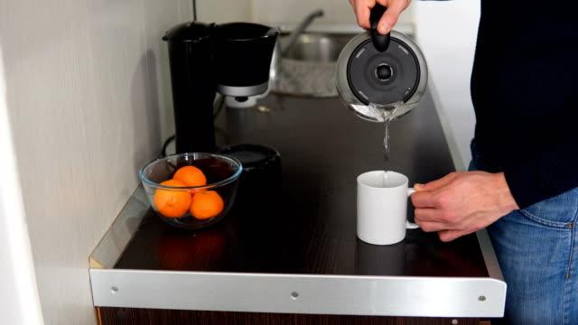 ハンサムな男が台所の家でお茶を飲みます。 - カップ点の映像素材/bロール