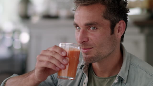 handsome man drinks healthy vegetable juice in a coffeehouse