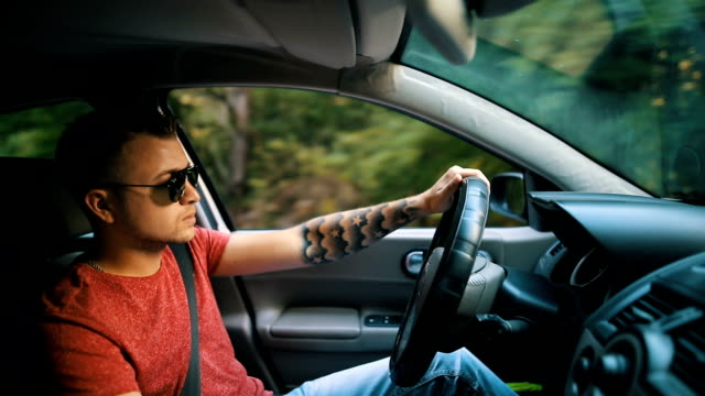 handsome man driving car - prestige car stock videos & royalty-free footage
