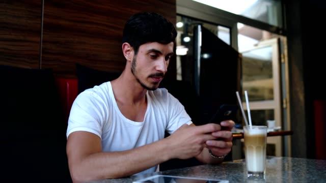stockvideo's en b-roll-footage met knappe man genieten van koffie en social media - ingesproken bericht