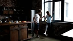 Handsome man inviting girl to dance in the kitchen