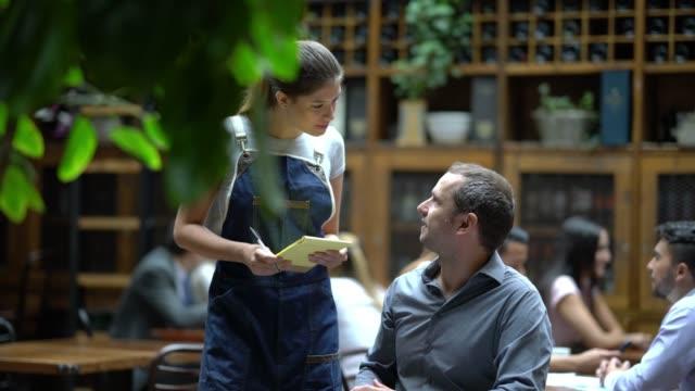 vídeos de stock e filmes b-roll de handsome man ordering something to a beautiful waitress who is ready to take notes with a notepad and a pen - empregada de mesa