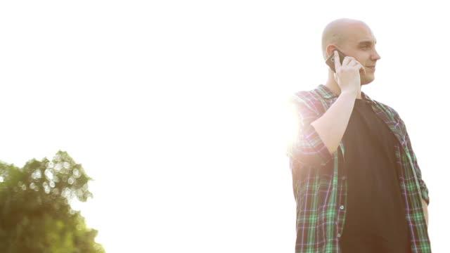 vídeos y material grabado en eventos de stock de hombre atractivo teléfono en el parque - cabeza afeitada