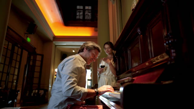 handsome man playing a piano for his wife at a restaurant - desire stock videos & royalty-free footage