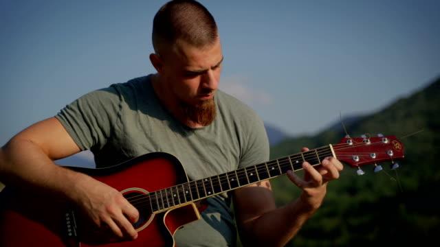 vídeos y material grabado en eventos de stock de guapo hombre tocando la guitarra afuera en las montañas - cuerda