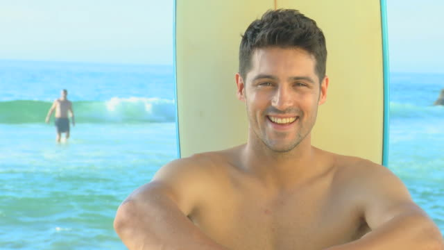 stockvideo's en b-roll-footage met handsome man posing in front of a surf board / cape town, western cape, south africa - ontbloot bovenlichaam