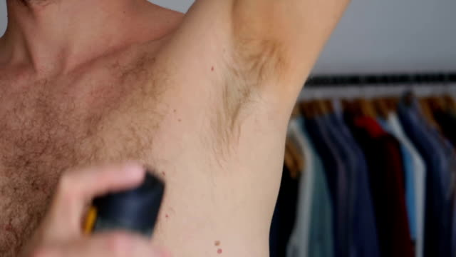 handsome man putting deodorant on his armpit - deodorant spray stock videos & royalty-free footage