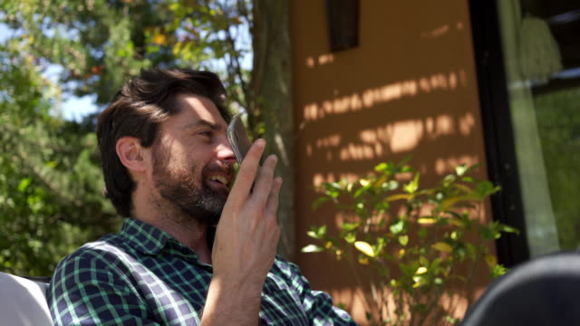 handsome mann aufnahme einer voicemail auf einem mobiltelefon - handsome people stock-videos und b-roll-filmmaterial