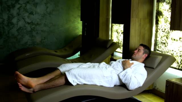 stockvideo's en b-roll-footage met knappe man rust in spa - in een handdoek gewikkeld