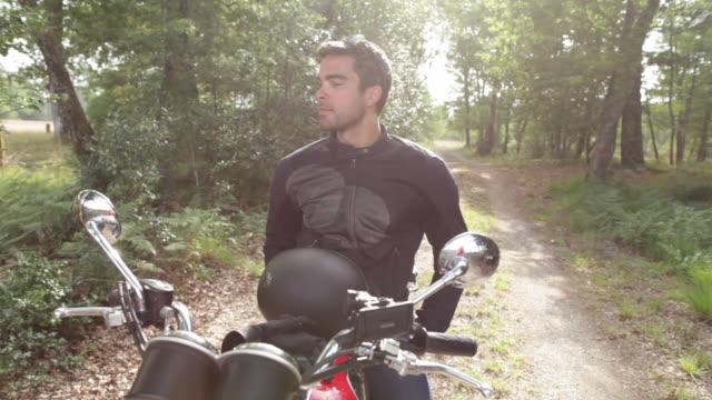 vídeos de stock e filmes b-roll de handsome man riding motorcycle on backroads in rural landscape - capacete moto