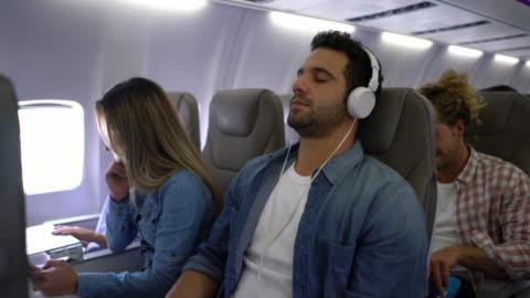 gut aussehender mann eine wiedergabeliste auswählen und setzen auf seine kopfhörer schließen seiner augen schauen entspannt während air flug - innenaufnahme stock-videos und b-roll-filmmaterial