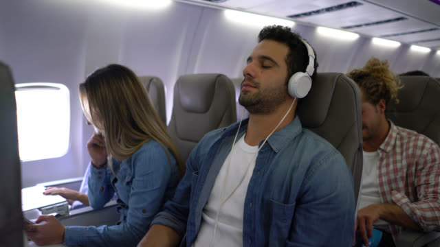 handsome man selecting a playlist and putting on his headphones closing his eyes looking relaxed during air flight - cuffia attrezzatura per l'informazione video stock e b–roll