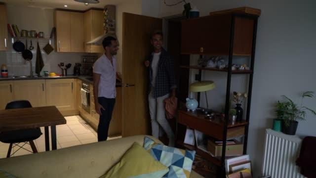 vídeos y material grabado en eventos de stock de un hombre guapo mostrando el apartamento a su nuevo compañero de cuarto - amistad masculina