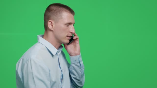handsome man talking on a mobile phone at greenscreen background - casual clothing stock videos & royalty-free footage