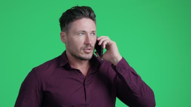 グリーンスクリーンの背景に携帯電話で話してハンサムな男 - ディレクター点の映像素材/bロール