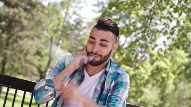 Handsome man talking on phone and vaping