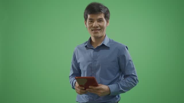 vídeos de stock, filmes e b-roll de mensagens de texto do homem bonito no tablet no fundo verde câmera lenta. - modelo web