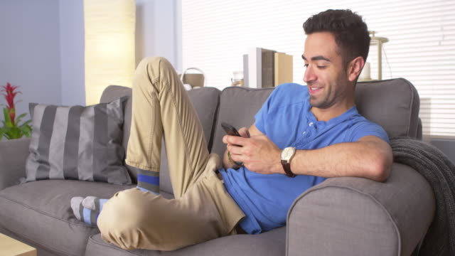Handsome man texting at home