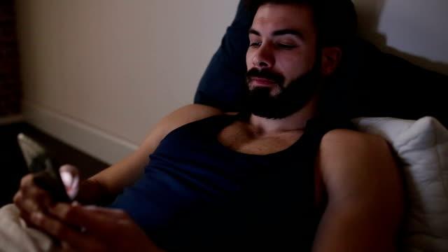 Gut aussehender Mann SMS bei Nacht und Lächeln